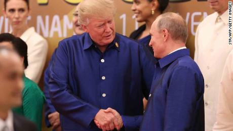 US President Donald Trump shakes hands with Russia's President Vladimir Putin (R) as they pose for a group photo ahead of the Asia-Pacific Economic Cooperation Summit leaders gala dinner in Vietnam in November.