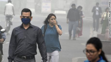 Indian people walk on a street as heavy smogs covers New Delhi on November 8, 2017. Delhi shut all primary schools on November 8 as pollution levels hit nearly 30 times the World Health Organization safe level, prompting doctors in the Indian capital to warn of a public health emergency. Dense grey smog shrouded the roads of the world's most polluted capital, where many pedestrians and bikers wore masks or covered their mouths with handkerchiefs and scarves.  / AFP PHOTO / DOMINIQUE FAGET        (Photo credit should read DOMINIQUE FAGET/AFP/Getty Images)