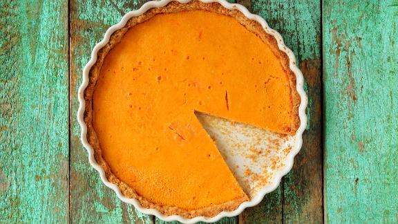 Fresh round bright orange homemade pumpkin pie in white baking dish on turquoise table overhead view