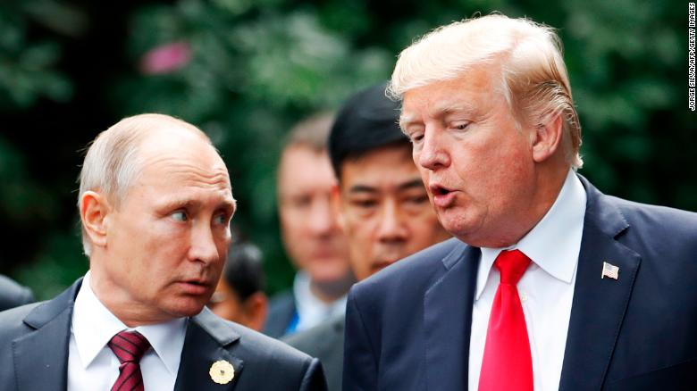 "US President Donald Trump (R) and Russia's President Vladimir Putin talk as they make their way to take the ""family photo"" during the Asia-Pacific Economic Cooperation (APEC) leaders' summit in the central Vietnamese city of Danang on November 11, 2017. World leaders and senior business figures are gathering in the Vietnamese city of Danang this week for the annual 21-member APEC summit. / AFP PHOTO / POOL / JORGE SILVA (Photo credit should read JORGE SILVA/AFP/Getty Images)"