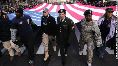 Soldiers, veterans and civilians carry an American Flag as they march in the Veterans Day Parade on November 11, 2017 in New York City.
