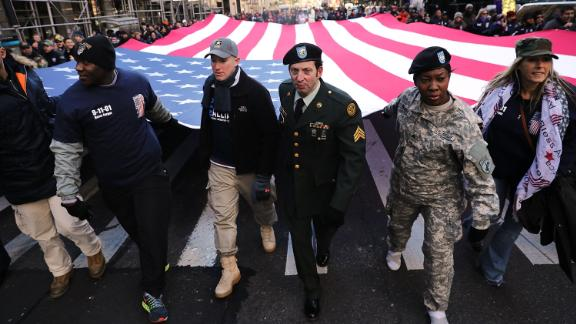NEW YORK, NY - NOVEMBER 11:  Soldiers, veterans and civilians carry an American Flag as they march in the Veterans Day Parade on November 11, 2017 in New York City. The largest Veterans Day event in the nation, this year's parade features thousands of marchers, including military units, civic and youth groups, businesses and high school bands from across the country and veterans of all eras. The U.S. Air Force is this year's featured service and the grand marshal is space pioneer Buzz Aldrin.  (Photo by Spencer Platt/Getty Images)