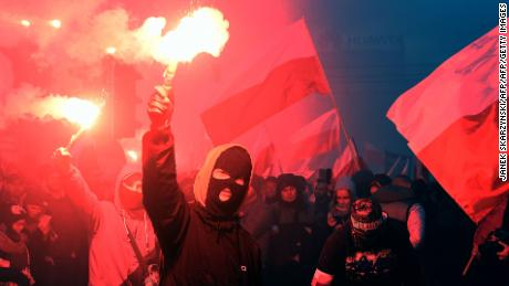 Demonstrators burn flares and wave Polish flags in last year's independence day march.