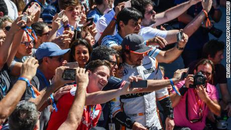 Alonso poses with fans for selfies before the Brazilian Formula One Grand Prix in 2017.
