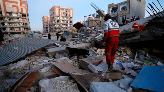 A rescue worker and his sniffer dog search for earthquake survivors in Sarpol-e-Zahab on November 13.