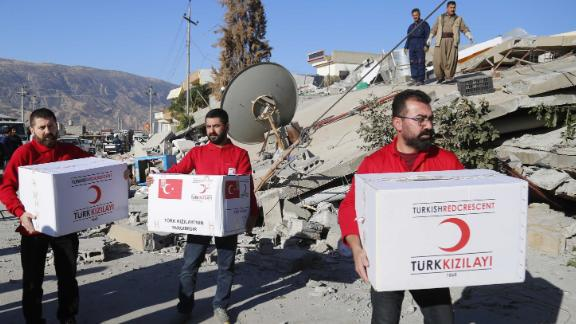 Members of the Turkish Red Crescent distribute aid to quake survivors in Iraq's Darbandikhan district on November 13.