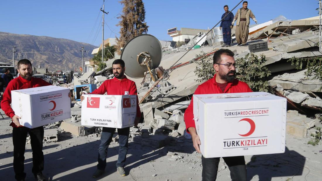 Members of the Turkish Red Crescent distribute aid to quake survivors in Iraq's Darbandikhan district on November 13.<br />