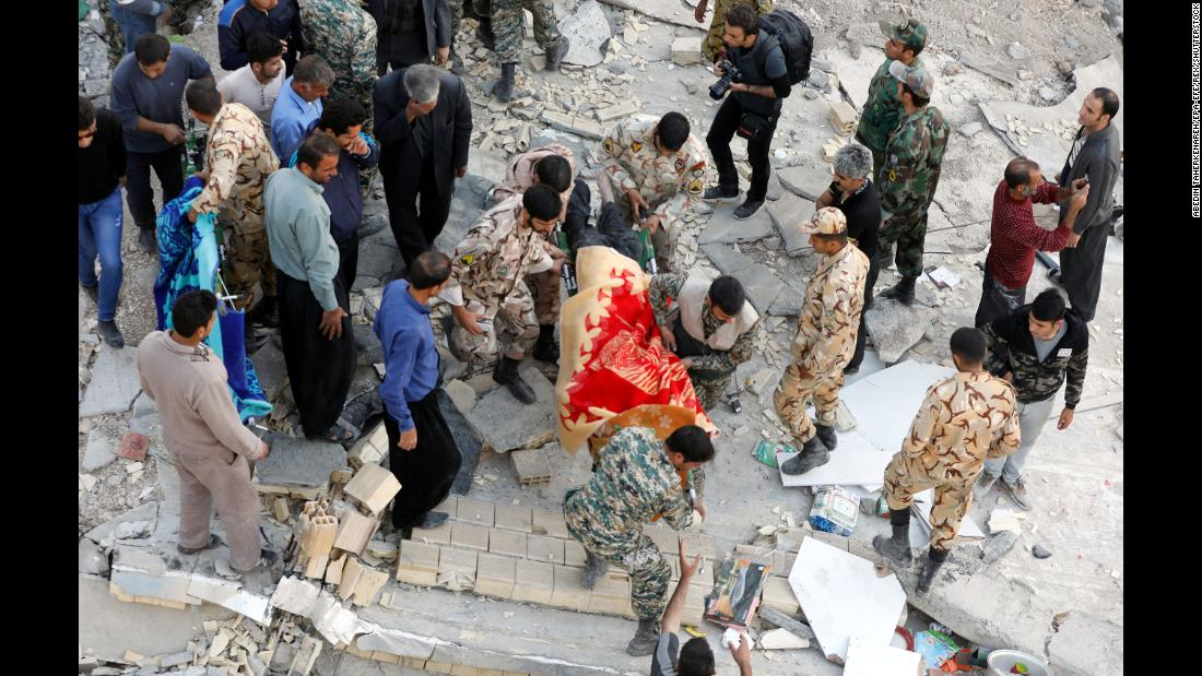 Rescue workers carry a victim's body out of a collapsed building in Sarpol-e-Zahab on November 13.
