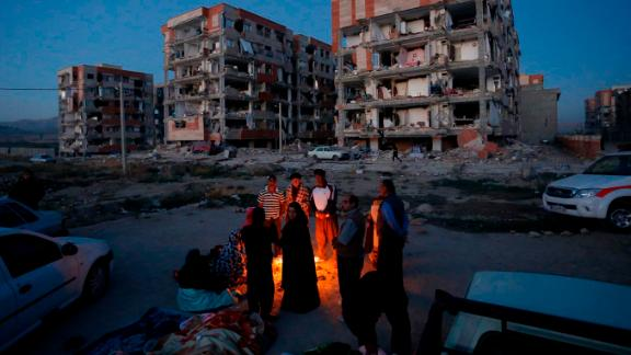 Residents of Sarpol-e Zahab huddle by a fire after the earthquake.