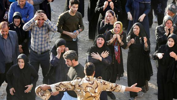 People try to get closer to the body of a relative who was killed in Sarpol-e Zahab.