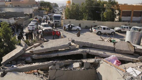 Emergency responders gather near collapsed buildings in the Darbandikhan district of Iraq's Sulaimaniya province.