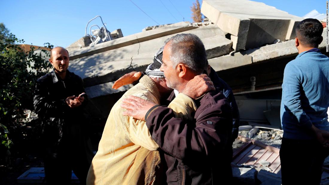 Two earthquake survivors embrace at the site of a collapsed building in Iraq's Darbandikhan district.