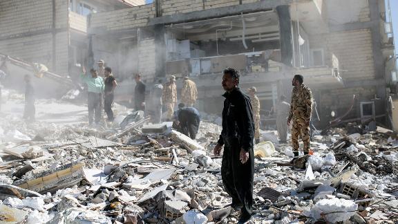 People walk through rubble in Sarpol-e Zahab on November 13.