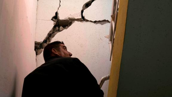 A man checks the interior of a damaged house after an earthquake in the city of Darbandikhan.
