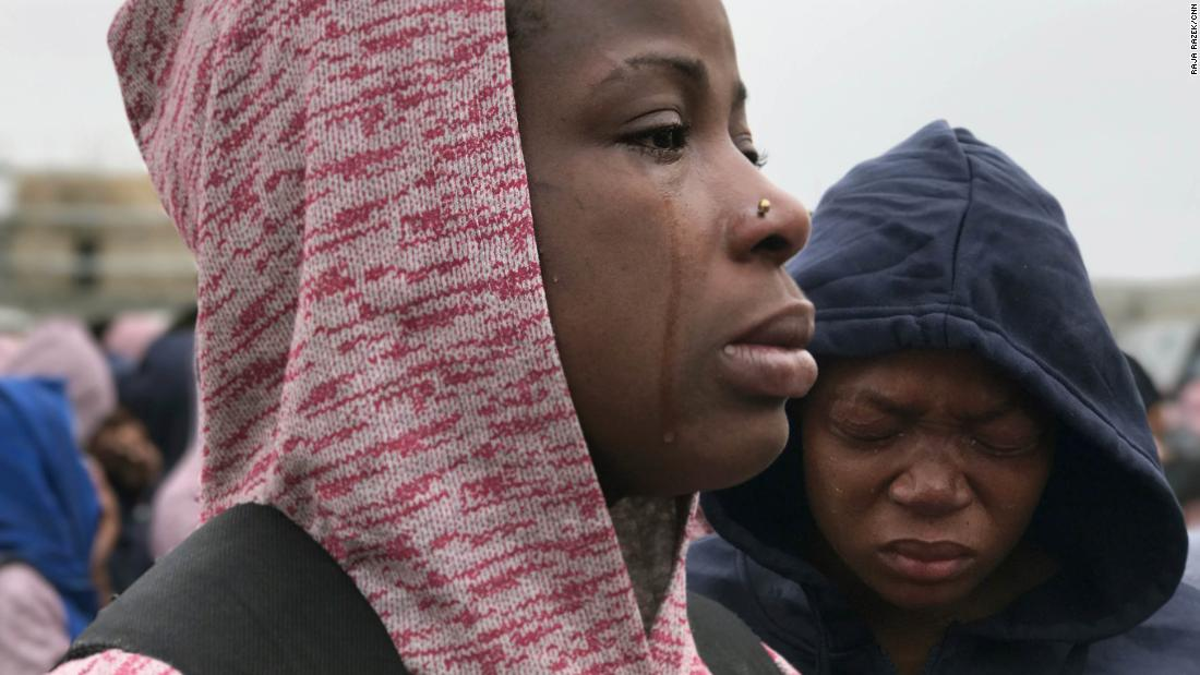 A woman cries as she is told she must leave her husband behind because he has yet to receive proper paperwork.