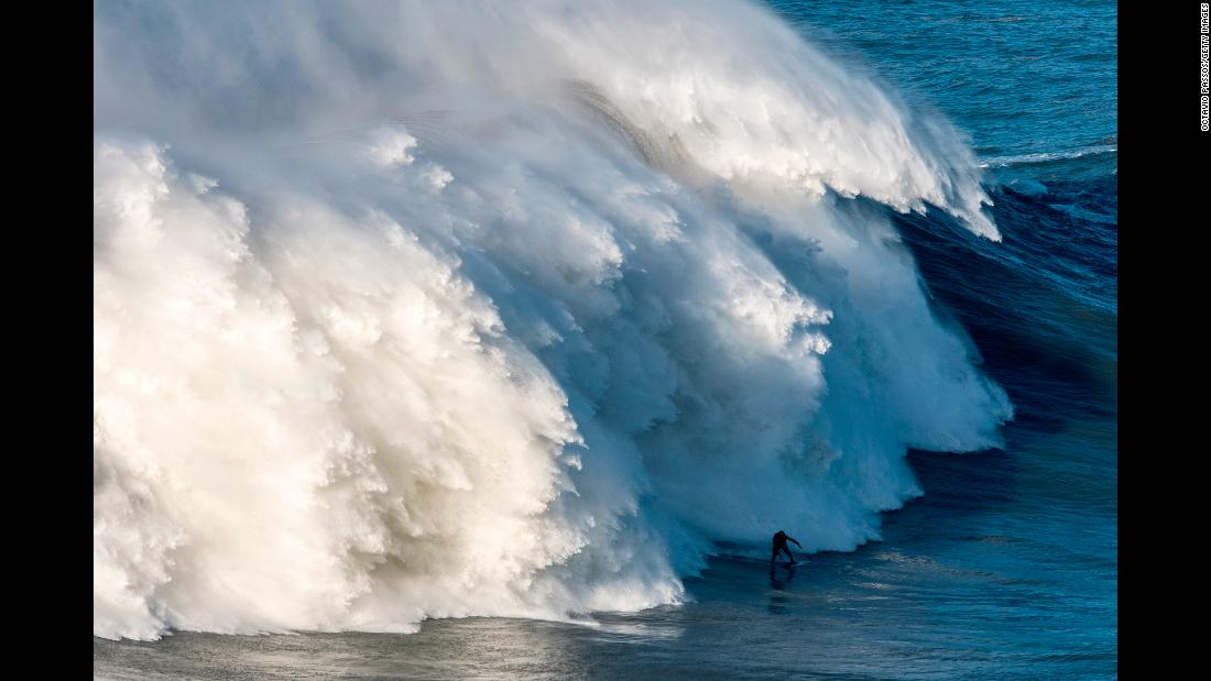 "A massive wave trails British surfer Andrew Cotton during a session in Nazare, Portugal, on Wednesday, November 8. Cotton suffered a broken back <a href=""http://www.cnn.com/videos/us/2017/11/10/surfer-breaks-back-after-massive-wipeout-lc-orig.cnn"" target=""_blank"">after being knocked off his board.</a>"