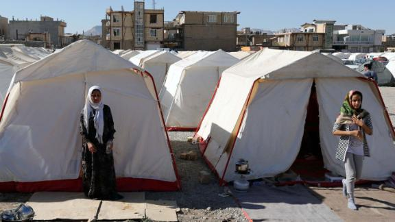 Iranian victims of the earthquake walk near tents erected for Iranian victims of the earthquake in the city of Sare Pole-Zahab, Kermanshah Province, Iran.