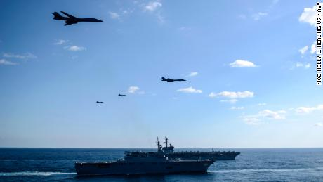 B-1B  bombers and F/A-18 strike fighters fly over a Japanese carrier and the USS Theodore Roosevelt.