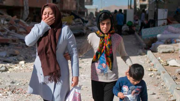 People react as they make their way through Sarpol-e Zahab, Iran, on Tuesday, November 14, two days after a magnitude 7.3 earthquake devastated the region along the Iran-Iraq border area. Hundreds were killed and thousands were hurt, officials said.