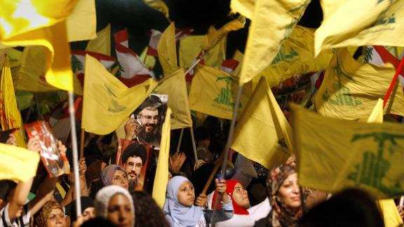 """Images of Hezbollah chief Hassan Nasrallah are seen among scores of Hezbollah and Lebanese national flags being waved by Hezbollah supporters during a ceremony to mark first anniversary of the war with Israel, 14 August 2007. Nasrallah reiterated to a mass rally broadcast live on television that his Shiite group had won a divine victory. """"Today is the anniversary of the divine victory,"""" Nasrallah told the thousands of men, women and children who had gathered in an empty lot of Beirut"""