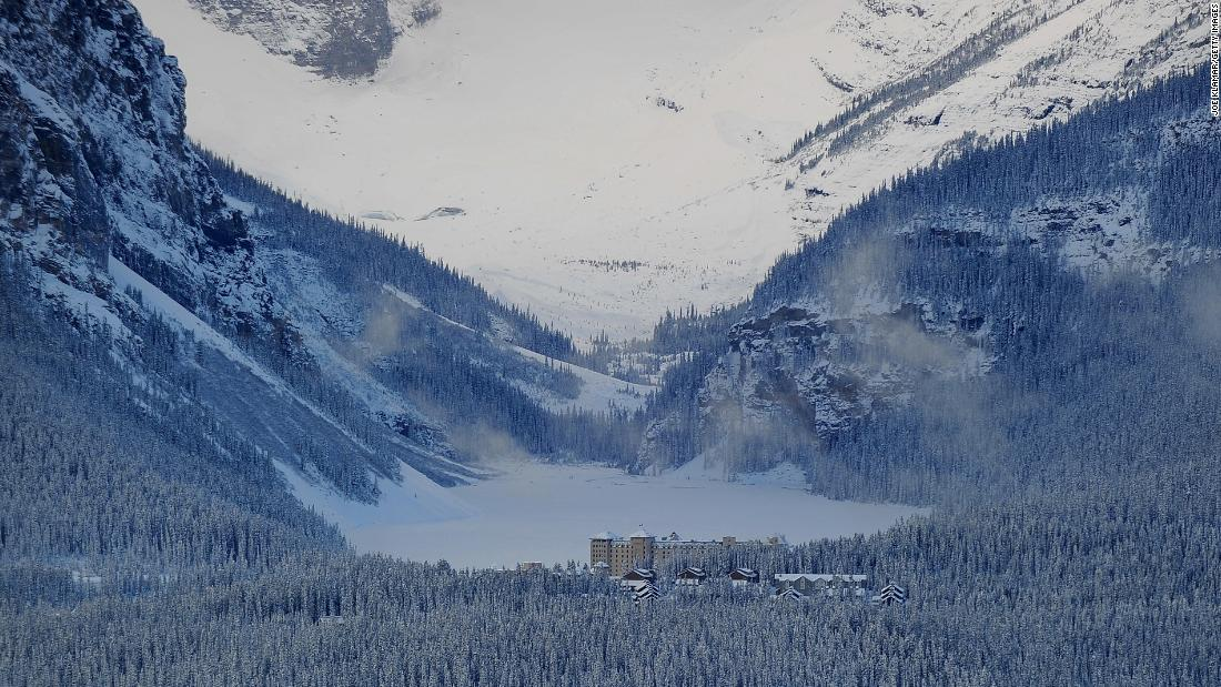 The iconic luxury Fairmont Chateau Lake Louise Hotel sits on the shore of the eponymous lake, which is snow covered in winter and a piercing emerald green in the summer.