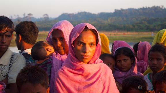 Rohingya refugees wait on the road side to hitchhike to nearby refugee camps. This nine-month pregnant woman had arrived with a larger group on fishing boats in the middle of the night to avoid detection by the Bangladesh coast guard. She said she did not have much to eat.