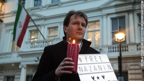 "Richard Ratcliffe holds a ""#Free Nazanin"" sign and candle during a vigil for his wife outside the Iranian Embassy in London in January 2017."