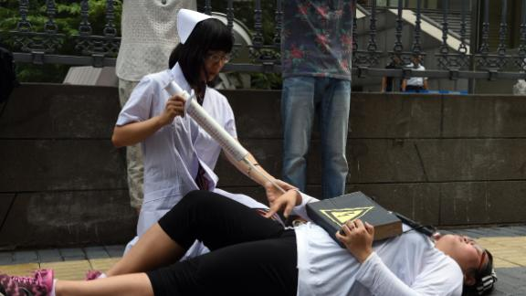 """Xiao Tie, executive director of the Beijing LGBT Centre, pretends to inject a patient with a mock syringe during a protest outside the Haidian District Court in Beijing on July 31, 2014. The court began hearing a landmark case on """"gay conversion"""" treatment July 31, as an activist in a nurse's uniform knelt over a patient, wielding a giant needle, outside. AFP PHOTO/Greg BAKER        (Photo credit should read GREG BAKER/AFP/Getty Images)"""