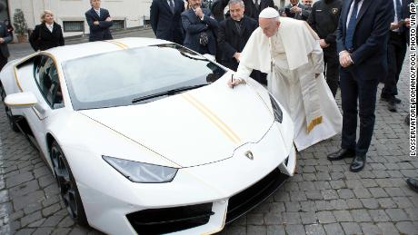 Pope Francis writes on the bonnet of a Lamborghini donated to him by the luxury sports car maker, at the Vatican, Wednesday, Nov. 15, 2017. The car will be auctioned off by Sotheby's, with the proceeds going to charities including one aimed at helping rebuild Christian communities in Iraq that were devastated by the Islamic State group. (L'Osservatore Romano/Pool Photo via AP)