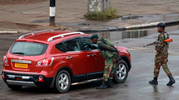 Soldiers inspect a vehicle on a road leading to Mugabe