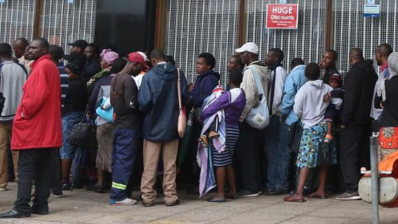 People wait Wednesday to withdraw cash outside a bank in Harare.