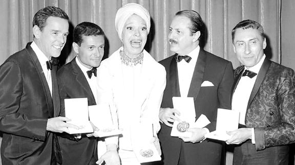 "Channing celebrates her Tony win alongside ""Hello Dolly!"" director Gower Champion, composer and lyricist Jerry Herman, producer David Merrick and costume designer Freddy Wittop in 1964. The original production won 10 Tony Awards."