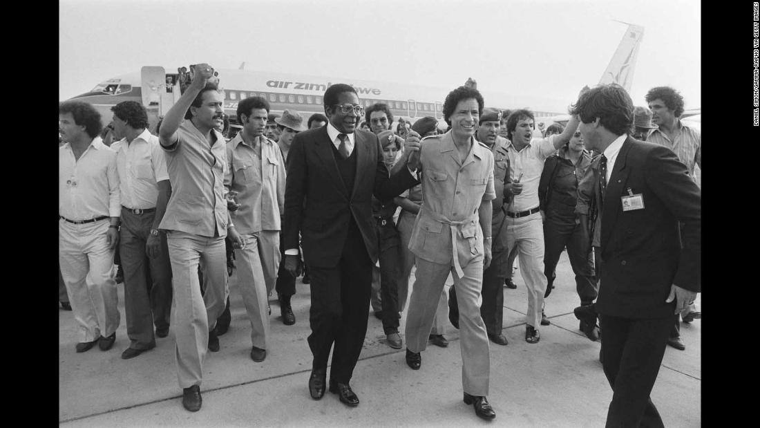 Mugabe holds hands with Libyan leader Moammar Gadhafi at the Organization of African Unity summit in August 1982.