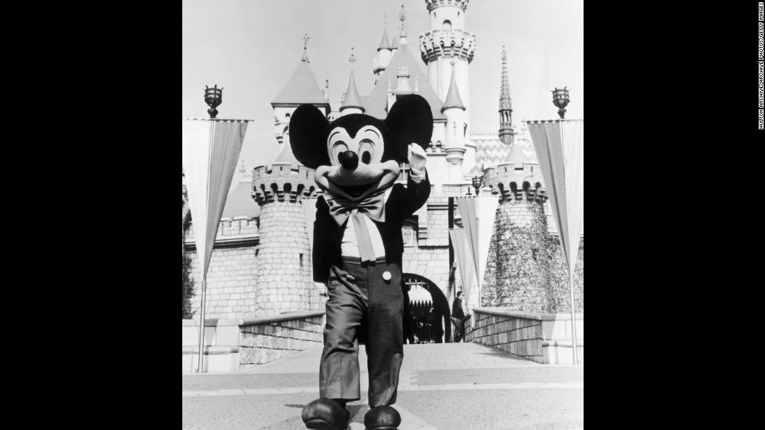 A person in a Mickey Mouse costume at the gate of the Magic Kingdom at the Disneyland theme park, Anaheim, California circa 1955.