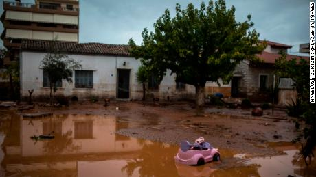 A toy car drifts on a flooded street next to a damaged house in Mandra on Wednesday.
