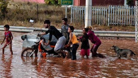 Youths make their way on a flooded street Wednesday in Mandra.