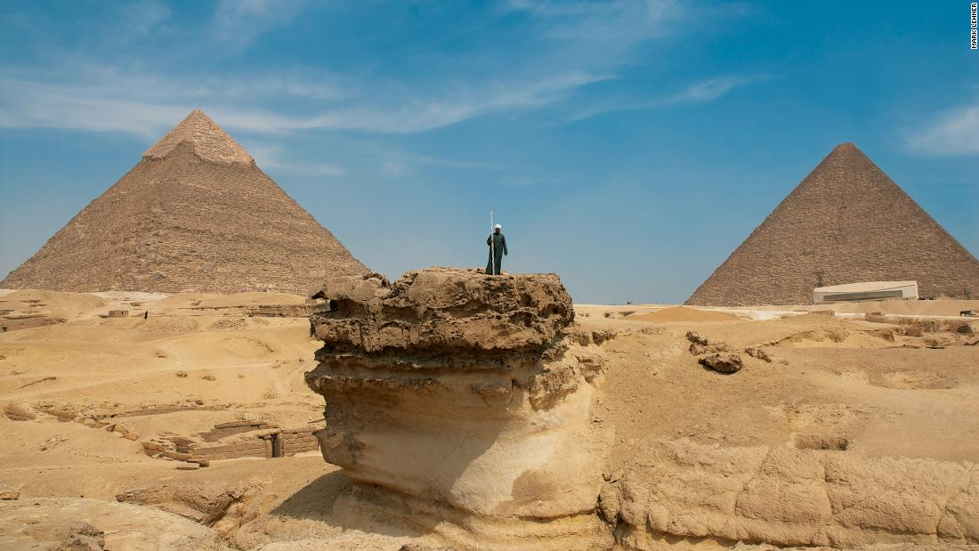 A man stands on the original surface level of the Giza plateau. Around it rock had been quarried for use on the surrounding structures. In the background, two of Giza's 4th dynasty pyramids. The Great Pyramid of Khufu covers an area of 5.3 hectares and was built with approximately 2.3 million stone blocks. <br />