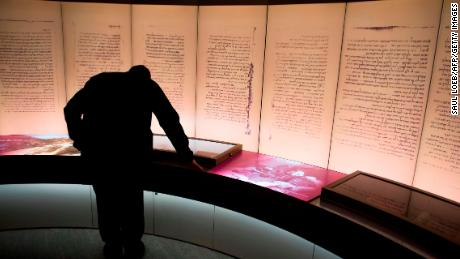 A visitors looks at an exhibit about the Dead Sea Scrolls during a media preview of the new Museum of the Bible.