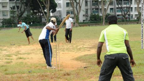 South Asian workers play a cricket game on the field next to Little India district in Singapore on December 15, 2013.