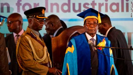Zimbabwe's President Robert Mugabe, right, arrives at the Zimbabwe Open University in Harare.