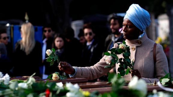 A woman places flowers on coffins during the service in Salerno.