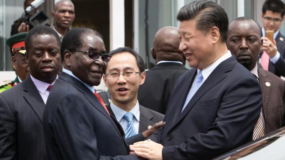 Xi shakes hands with Mugabe as he arrives on December 1 in Harare.