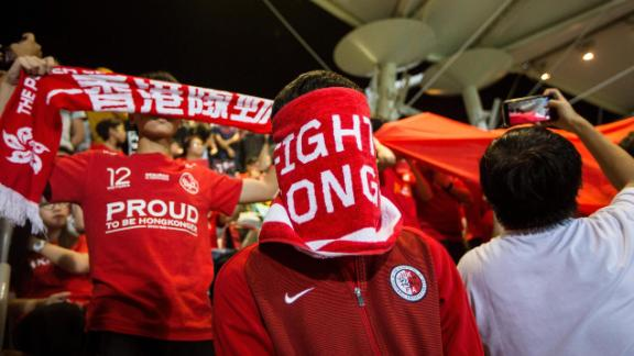 A Hong Kong fan covers his face during the Chinese national anthem before the match between Hong Kong and Bahrain on November 9, 2017.