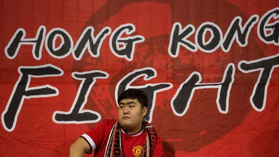 A Hong Kong fan sits in front of a flag before an international friendly football match between Hong Kong and Bahrain at Mong Kok Stadium in Hong Kong on November 9, 2017.
