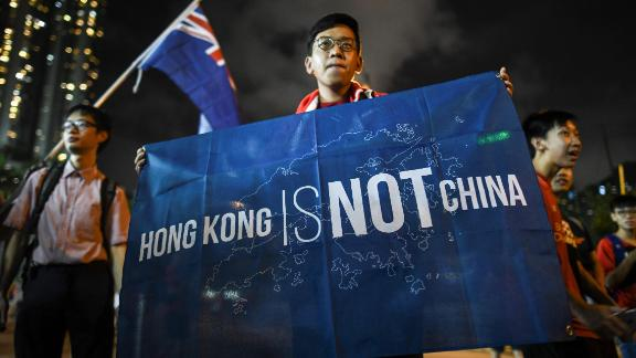 """In this October 10, 2017 photograph, a flag that reads """"Hong Kong is not China"""" is displayed by a local football fan in front of the old British colonial flag after a match between Hong Kong and Malaysia in Hong Kong."""