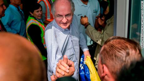 The mayor of Caracas, Antonio Ledezma, 62, greets followers Friday at El Dorado International Airport in Bogota, Colombia, before embarking to Spain after escaping house arrest in the Venezuelan capital.