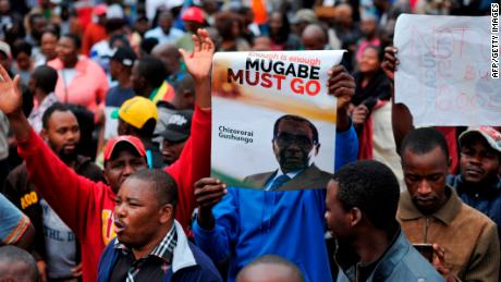 Demonstrators hold anti-Mugabe placards and shout slogans during a protest march demanding the resignation of Zimbabwe's president on November 18, 2017 in Harare. Zimbabwe was set for more political turmoil November 18 with protests planned as veterans of the independence war, activists and ruling party leaders called publicly for President Robert Mugabe to be forced from office. / AFP PHOTO / -        (Photo credit should read -/AFP/Getty Images)