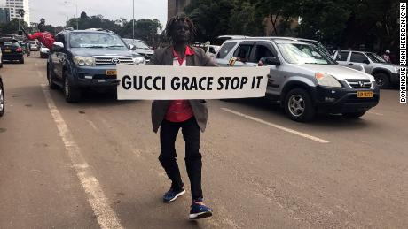 A demonstrator carries a sign directed at first lady Grace Mugabe.