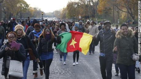 "A woman holds a flag of Cameroon during a march against ""slavery in Libya"" on November 18 in Paris."