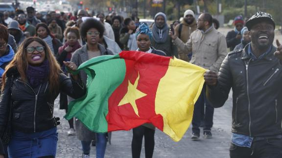 """A woman holds a flag of Cameroon during a march against """"slavery in Libya"""" on November 18 in Paris."""